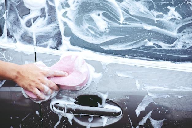 Homme de gens tenant une éponge rose à la main pour laver la voiture. nettoyage des pneus de roue. concept de lavage de voiture propre.