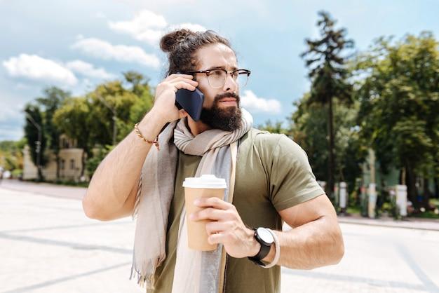 Homme gentil sérieux mettant un téléphone à son oreille tout en passant un appel téléphonique