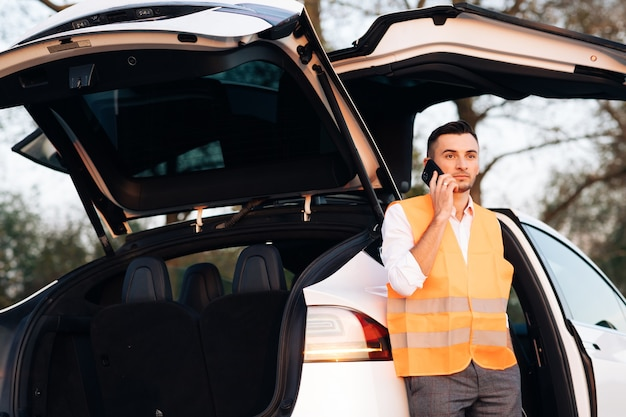 Homme avec gilet réfléchissant appelant par téléphone au sujet d'une panne dans sa voiture électrique