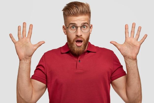 Homme gingembre mal rasé avec une expression stupéfaite, garde les paumes levées, fait des gestes actifs