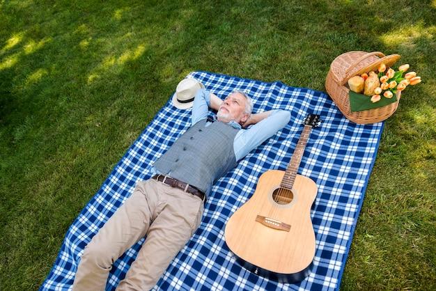 Homme grand angle, couché sur une couverture