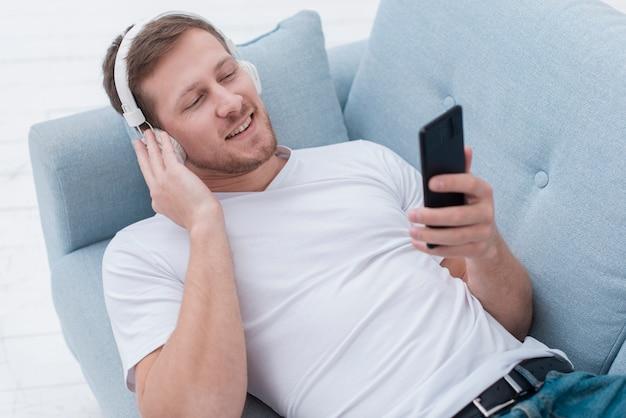 Homme grand angle, écouter de la musique sur les écouteurs