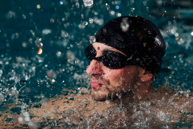 Homme grand angle, lunettes protectrices, casquette, natation