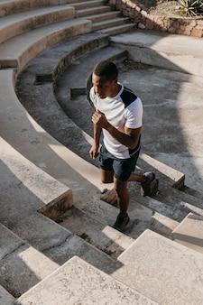 Homme grand angle qui court dans les escaliers