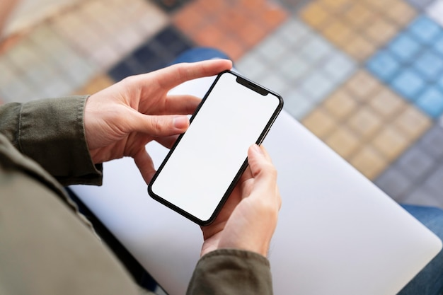 Homme grand angle regardant son téléphone avec écran vide