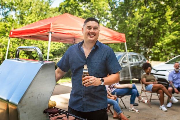 Homme grillant sur le barbecue lors d'une fête de hayon