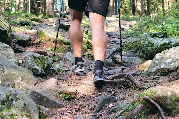 L'homme grimpe en baskets en action extérieure. vue de dessus de la botte de randonnée sur le sentier. jambes en gros plan en jeans et chaussures de randonnée sportive sur les pierres rocheuses de la forêt de montagne.