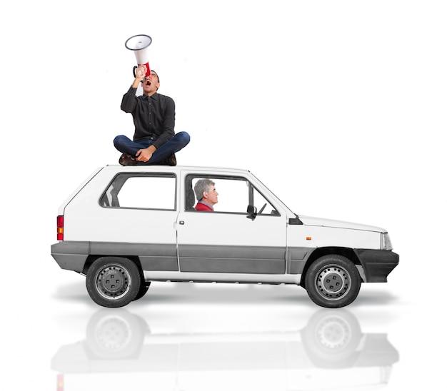 L'homme a grimpé sur le toit d'une voiture criant pour un mégaphone