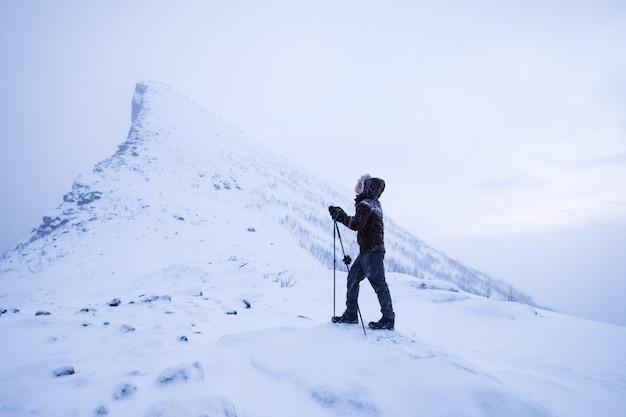 Homme grimpeur avec bâtons de trekking debout sur le sommet de la montagne enneigée