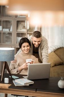 Homme en gris. un mec aux cheveux noirs rayonnant étreignant sa femme tout en se tenant derrière et à la recherche d'informations dans un ordinateur portable