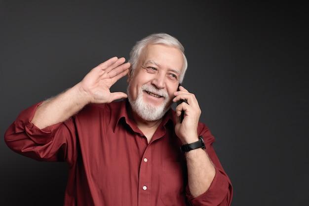 Homme grisonnant charismatique en chemise rouge riant et parlant au téléphone