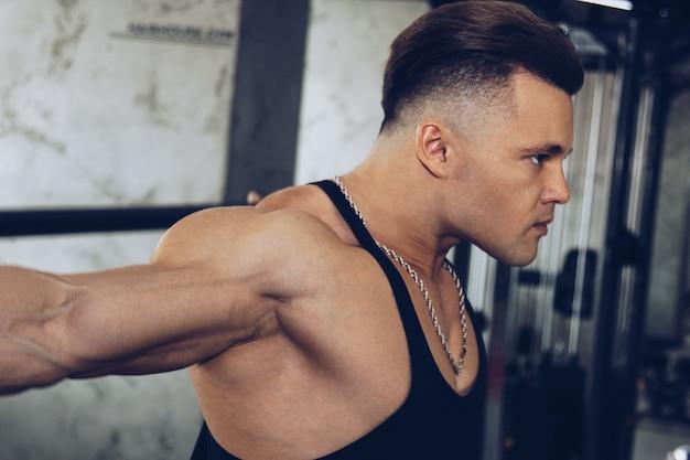 Un homme avec de gros muscles fait de l'haltérophilie dans la salle de gym. un athlète gonflé fait du sport sur des simulateurs de poids lourds. exercices sportifs.