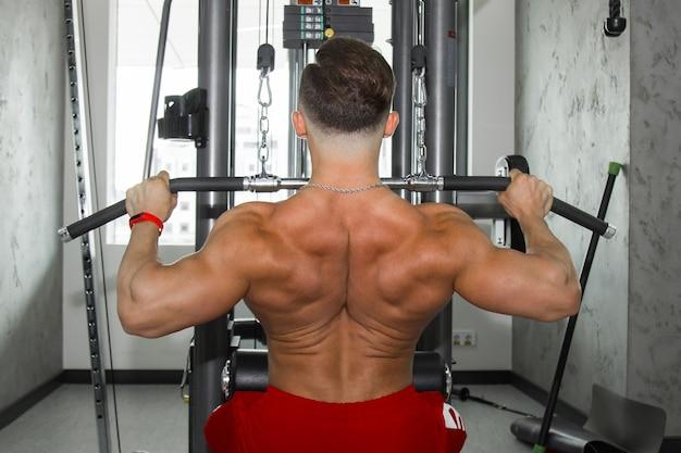 Un Homme Avec De Gros Muscles Fait De L'haltérophilie Dans La Salle De Gym. Un Athlète Gonflé Fait Du Sport Sur Des Simulateurs De Poids Lourds. Exercices Sportifs. Photo Premium