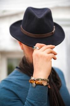 Un homme en gros plan d'un chapeau. bracelets en pierres sur la main d'un homme.