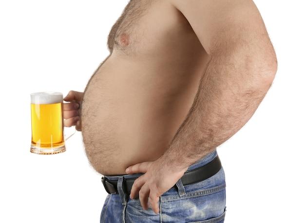 Homme avec gros ventre tenant un verre de bière sur fond blanc