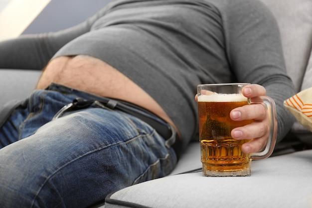 Homme avec gros ventre tenant un verre de bière à la maison
