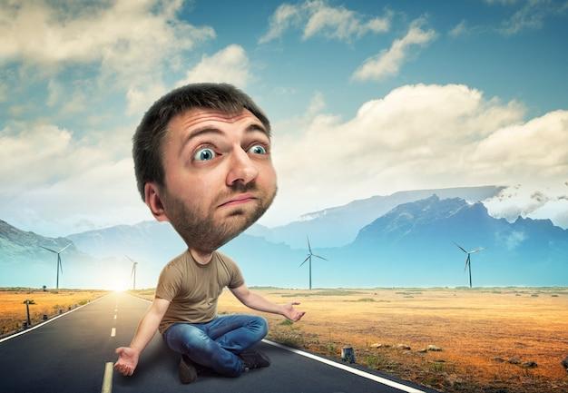 Homme avec une grosse tête assis sur la route