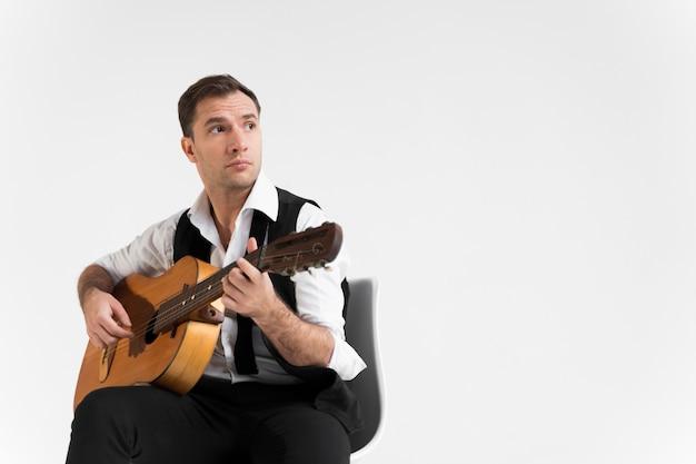 Homme avec guitare dans l'espace de copie de studio