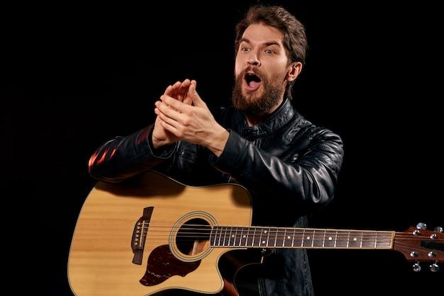 Un homme avec une guitare dans ses mains veste en cuir musique performance rock star de style moderne mur sombre.