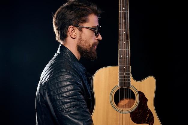 Un homme avec une guitare dans ses mains veste en cuir performance musicale rock star style moderne fond sombre