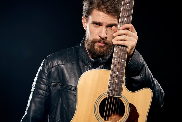 Un homme avec une guitare dans ses mains veste en cuir performance musicale rock star style moderne sombre