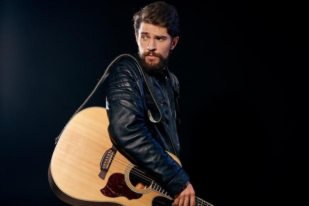 Un homme avec une guitare dans ses mains veste en cuir performance musicale rock star
