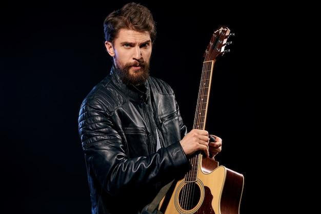 Homme avec une guitare dans ses mains veste en cuir