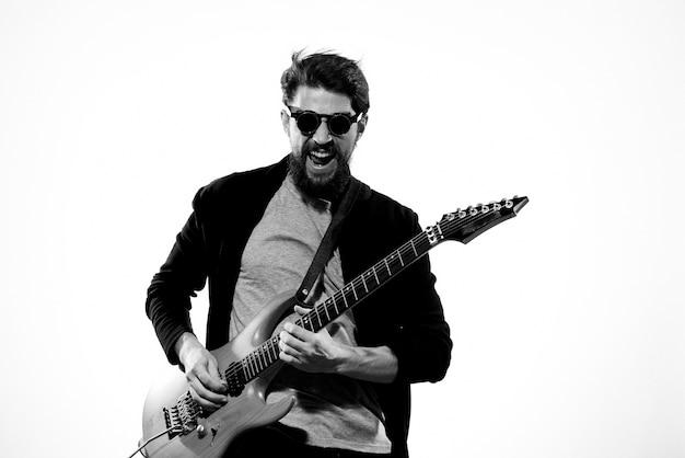 Homme avec guitare en mains musicien rock star performance lifestyle fond clair.
