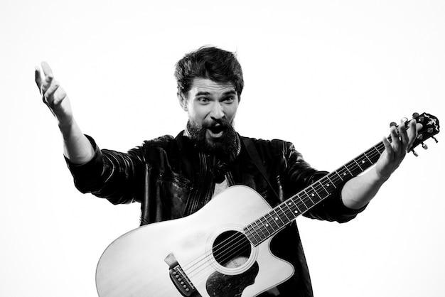 Homme avec guitare portant une veste en cuir