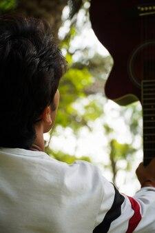 Un homme avec guitare avec t-shirt logo usa