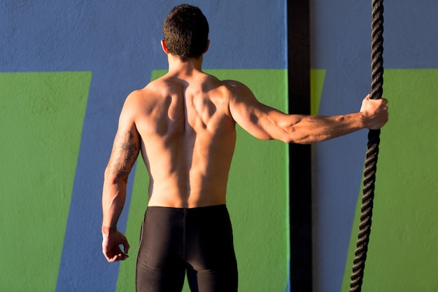 Homme de gym crossfit tenant à la main une corde d'escalade