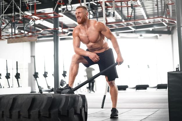 Homme gym hammer hit tracteur roue frapper énorme pneu athlète homme sportif moyen adulte beau sportif bodybuilder haltérophile corps idéal