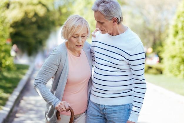 Homme habile attentionné, prenant soin de sa vieille femme et l'aidant à faire des pas en marchant dans la rue