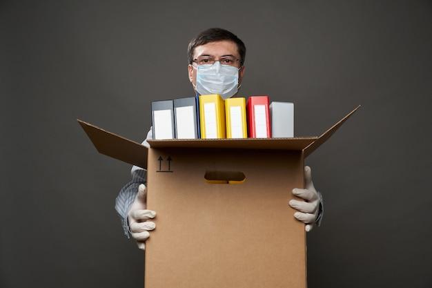 Un homme habillé comme un homme d'affaires tient une boîte avec des trucs de bureau, des documents, qui pose en studio sur fond gris, un masque médical et des gants de protection, des lunettes, une chemise et une cravate