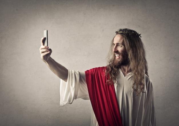 Homme habillé comme jésus prenant un selfie