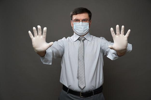 Un homme habillé en homme d'affaires montrant l'arrêt avec la paume de sa main, fond gris, masque médical et gants de protection, lunettes, chemise et cravate - concept de quarantaine et protection antivirus