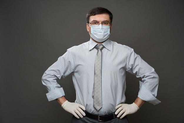 Un homme habillé en homme d'affaires, posant en studio sur fond gris, masque médical et gants de protection, lunettes, chemise et cravate - concept de quarantaine et protection antivirus