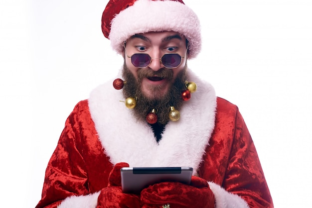 Un homme habillé en père noël avec admiration regarde un livre électronique entre ses mains copy-space