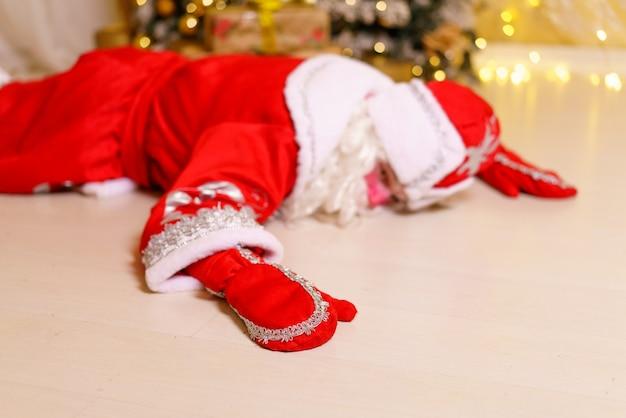 Un homme habillé en père noël est allongé sur le sol près d'un arbre de noël avec des cadeaux dort ou se repose