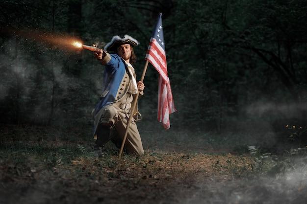 Homme habillé en soldat de la guerre d'indépendance des états-unis vise à partir de pistolet avec drapeau