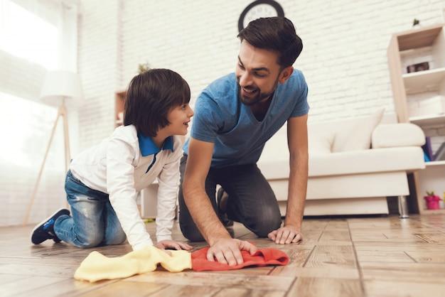 Un homme habitue le garçon à la propreté.