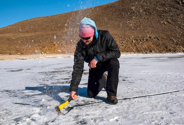 Un homme hache la glace avec une hache sur un lac gelé en hiver
