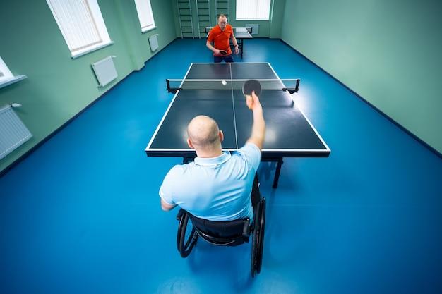 Homme handicapé adulte dans un fauteuil roulant jouer au tennis de table avec son entraîneur