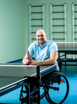 Homme handicapé adulte dans un fauteuil roulant à jouer au tennis de table