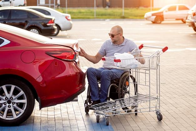 L'homme handicapé adulte dans un fauteuil roulant met des achats dans le coffre d'une voiture dans un parking de supermarché