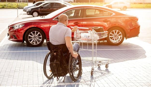 L'homme handicapé adulte dans un fauteuil roulant pousse un chariot vers une voiture dans un parking de supermarché