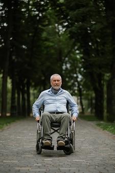 Homme handicapé adulte en fauteuil roulant marchant dans le parc d'été. personnes paralysées et handicaps, dépassement du handicap. loisirs masculins handicapés dans un lieu public
