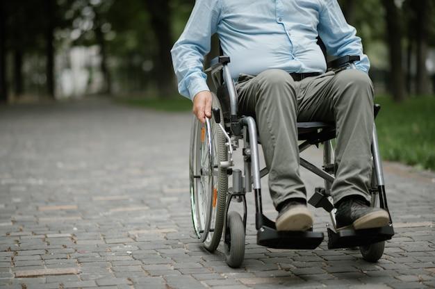 Homme handicapé adulte en fauteuil roulant se reposant dans le parc