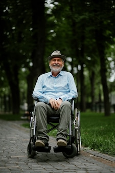 Un homme handicapé adulte en fauteuil roulant tient une feuille de papier