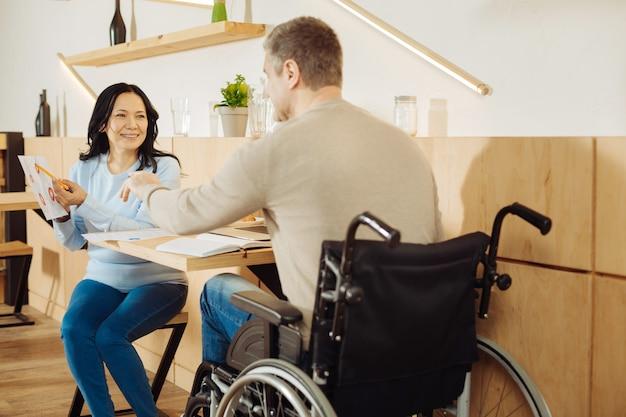 Homme handicapé blond bien construit et une jolie femme aux cheveux noirs gaie souriant et discutant du travail alors qu'il était assis à la table dans un café
